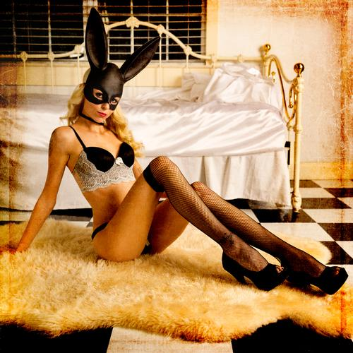 Batwoman Foxy lady poses in a black and white French maids costume and fishnet stockings sitting with her legs open on a sheepskin rug in front of a daybed with white satin sheets.